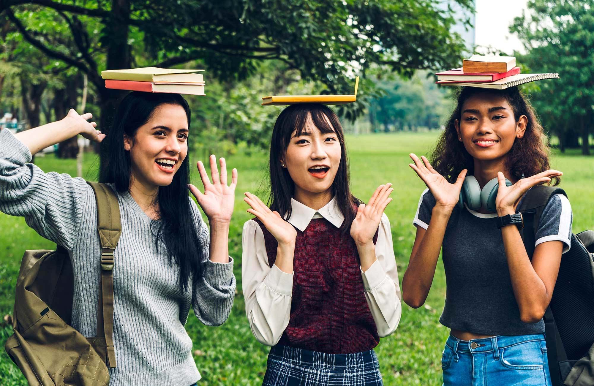 girls-student-group-standing-park-books